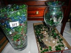 A vase and a tray of coloured glass beads.