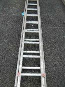 An double ladder with wooden sides and aluminium treads.