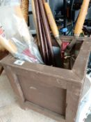 A cube wooden planter with a collection of walking sticks