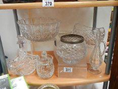A shelf of good cut glass items.