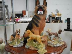 A large German Shepherd and three other dog figures.