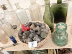 A collection of clean decorative bottles including a basket of screw tops
