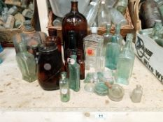 A collection of brown/clear bottles with a large chemist poison bottle