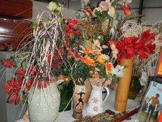 A large lot of artificial flowers in vases.