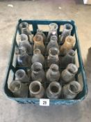 A crate with 20 various clear glass milk bottles