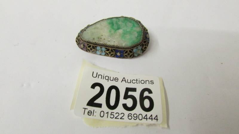 A carved jade brooch with enamelled coloured flowers to edges.