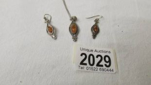 A silver pendant with matching earrings.