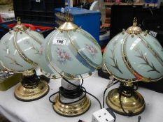 Three brass table lamps.