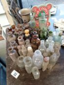 A lot of brown, green & clear small potion bottles with a jug etc.