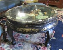 A circular Chinese lacquered table with applied figures under glass top (collect only).