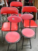 5 kitchen chairs with red seats.