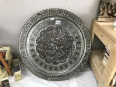 A large round Indian copper tray with relief decoration & silver plated finish