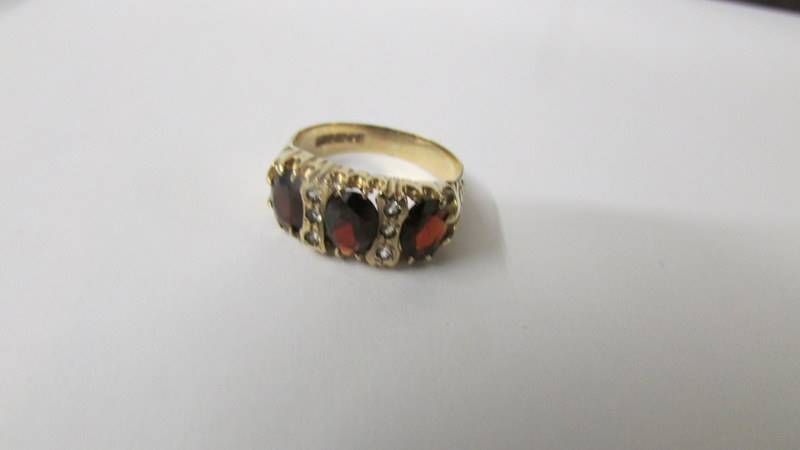 A 9ct gold ring set red stones and diamonds, size Q, 4 grams total. - Image 2 of 3