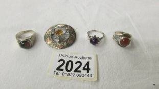 A silver thistle brooch and three silver rings.