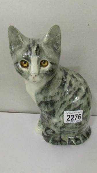 A signed pottery cat with glass eyes.