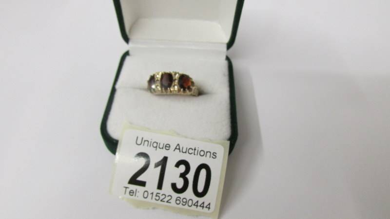 A 9ct gold ring set red stones and diamonds, size Q, 4 grams total.