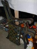 A pair of cast iron bench ends with seat plate.