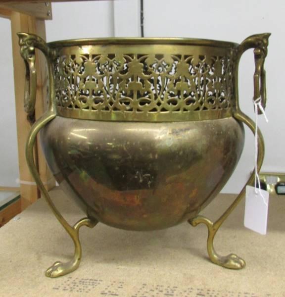 An Edwardian art nouveau brass three footed jardeniere.