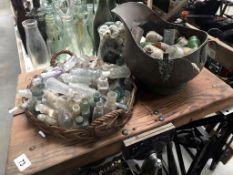 A wicker basket, glass jar & copper bucket of bottles, tops & lids etc.