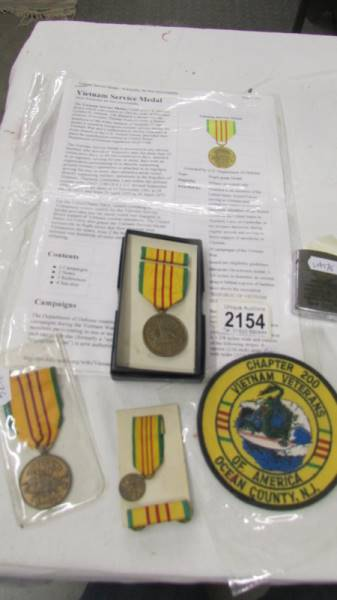 2 American Vietnam service medals together with a miniature service medal and a Zippo Vietnam