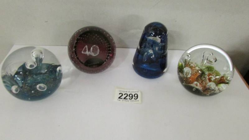 Four Caithness glass paperweights.