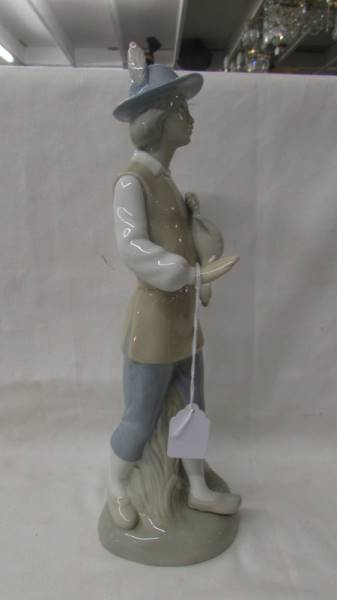 A Porcelarias Miguel Requienna Valencia porcelain figure of a hunter with a duck.