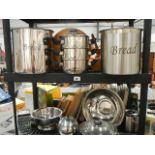 Two shelves of stainless steel kitchen ware.