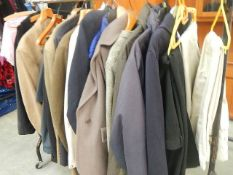 A rail of assorted suits, jackets and other clothing.