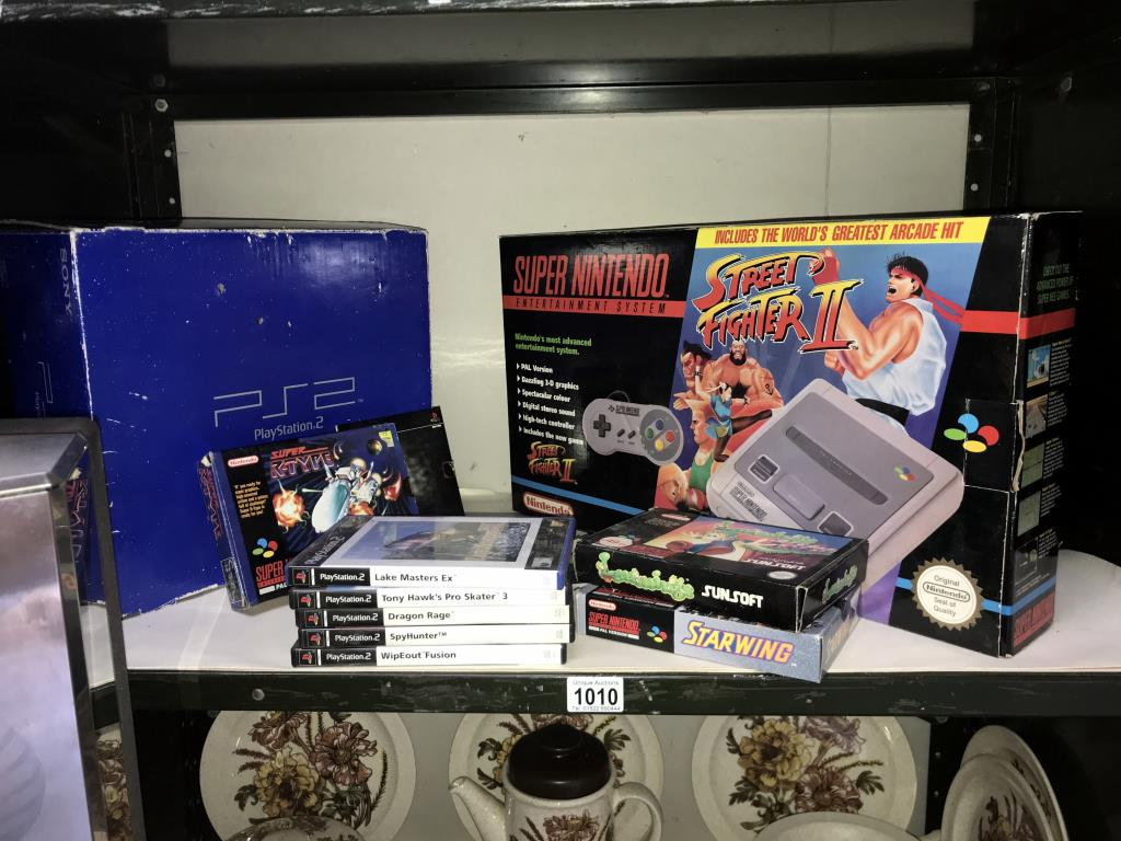 A PS2 PlayStation and a Super Nintendo system with selection of games