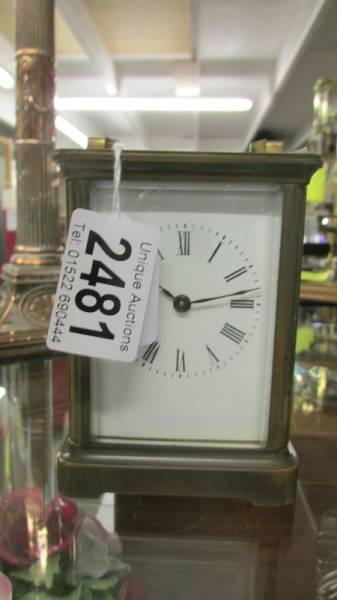 A brass carriage clock with key.