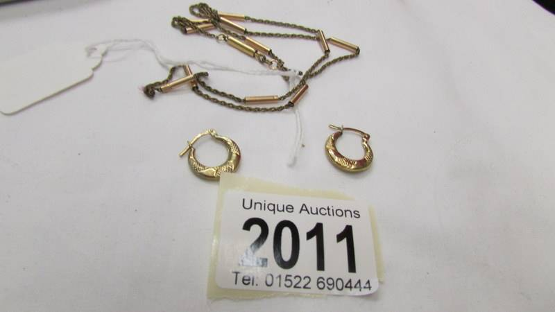 A pair of 9ct gold hoop earrings and a yellow metal chain.