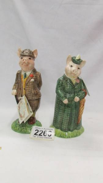 Two Beswick figurines - The Gentleman Pig and The Lady Pig.