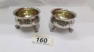 A pair of Victorian silver plate salts with ball and claw feet and decorative design.