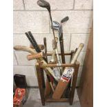 A 1930's oak stitch stand & sports equipment including golf clubs & cricket bats etc.