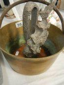An old brass jam pan and a sculpture.