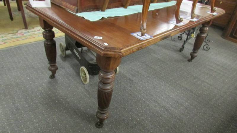 A Victorian mahogany extending dining table with one leaf.