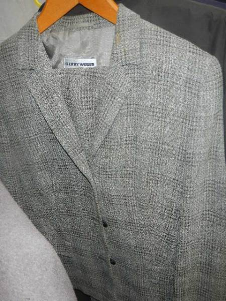 A rail of assorted suits, jackets and other clothing. - Image 5 of 11
