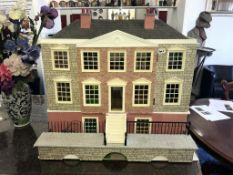 A large doll's house modelled on a George III circa 1790 mansion, electric fittings.