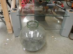 A TV table and a glass carboy.