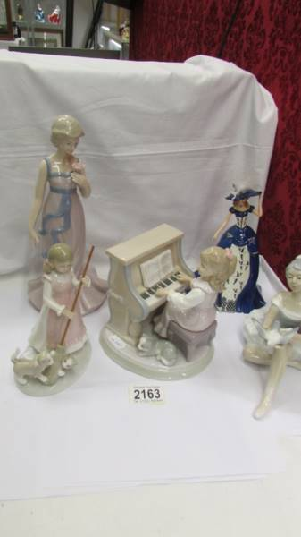 Three Lladro figures including girl at piano,