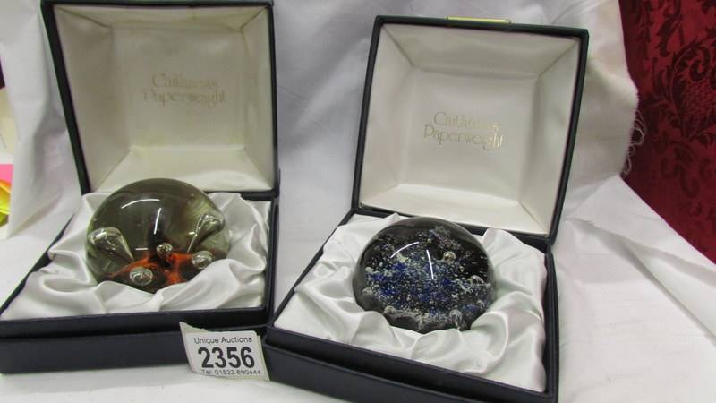 Two boxed Caithness paperweights.