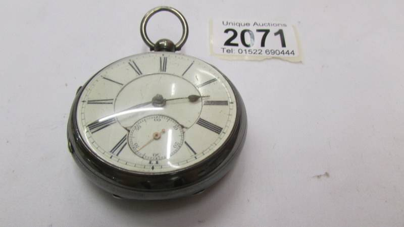 A silver pocket watch with key. - Image 2 of 2