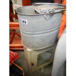 A metal bathroom cabinet and a mop bucket.