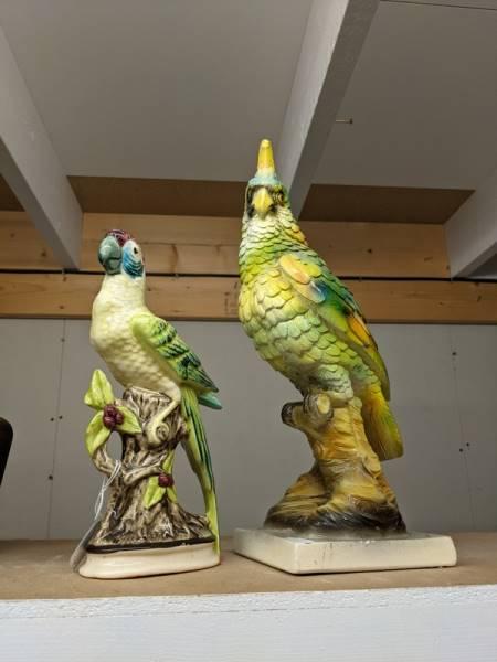 Two ceramic parrots.