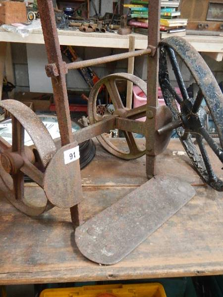 An old metal trolley and a cast wheel. - Image 2 of 2