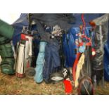 A large quantity of golf bags and clubs.