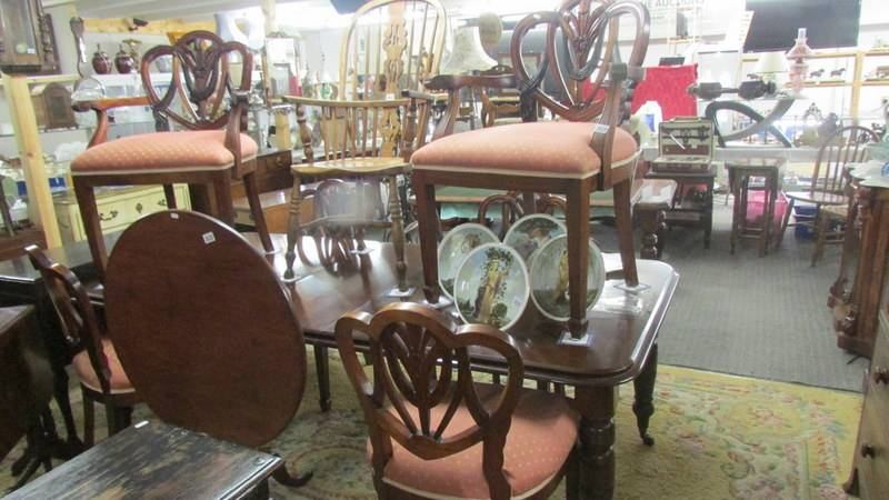 A mahogany extending dining table with three leaves and a set of 6 dining chairs.