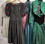 A collection of five evening gowns of varying designs and lengths,