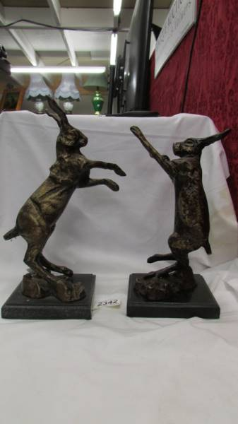 A pair of Bronzed spelter boxing hares on marble bases.