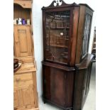 A dark wood stained corner cabinet with astragal glazed door.